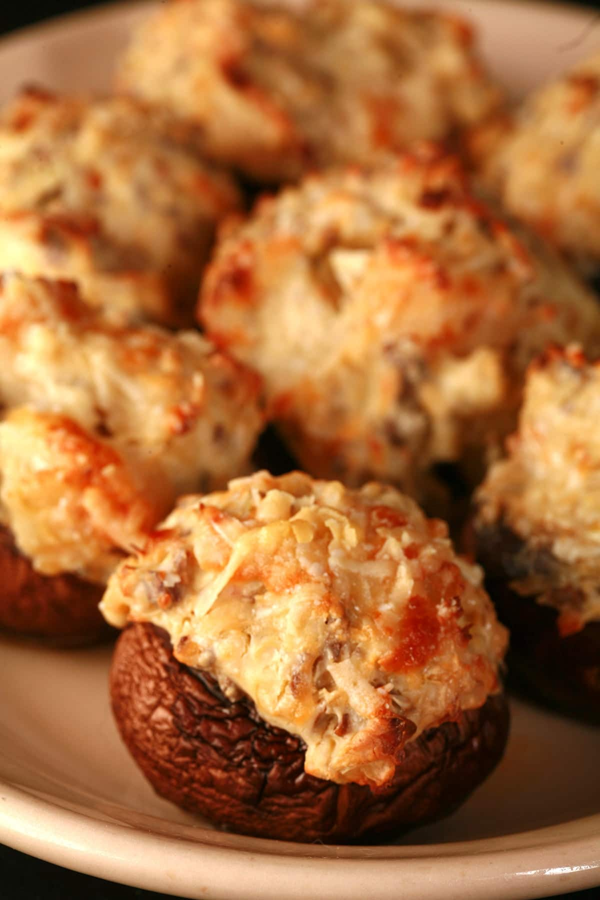 Golden brown shrimp and artichoke stuffed mushrooms on a tan plate.