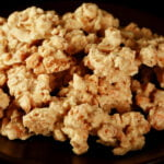 Close up view of homemade Clodhoppers candy: clusters of cashew pieces, graham crackers, and white chocolate.