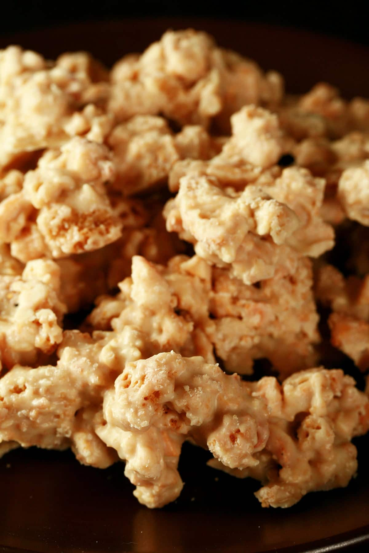 Close up view of a bowl of candy made from clusters of cashews, graham grackers, and white chocolate.