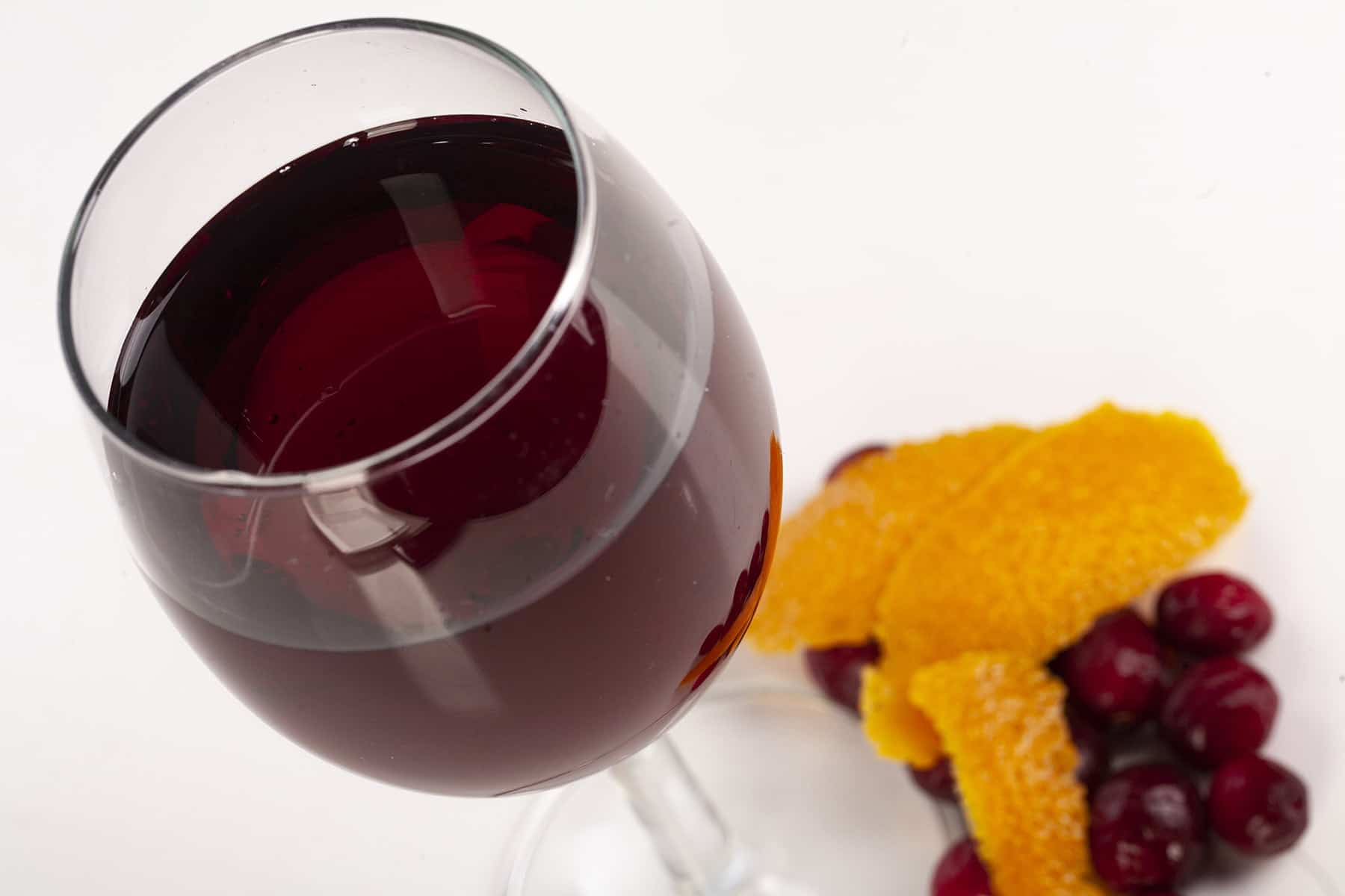 A close up view of a wine glass with with a deep red wine. There are cranberries and orange peels at the base of the glass, against a white background.