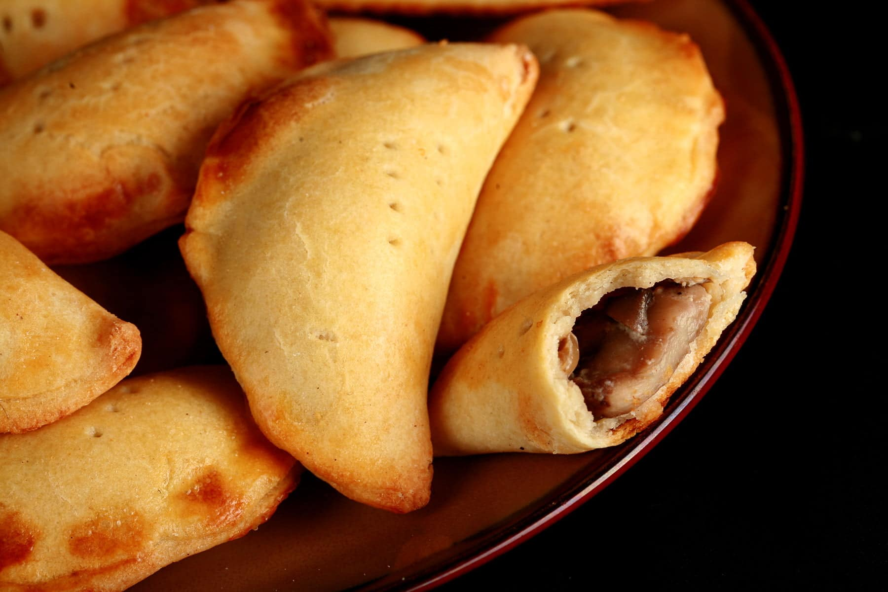 A plate piled with golden brown mushroom turnovers.