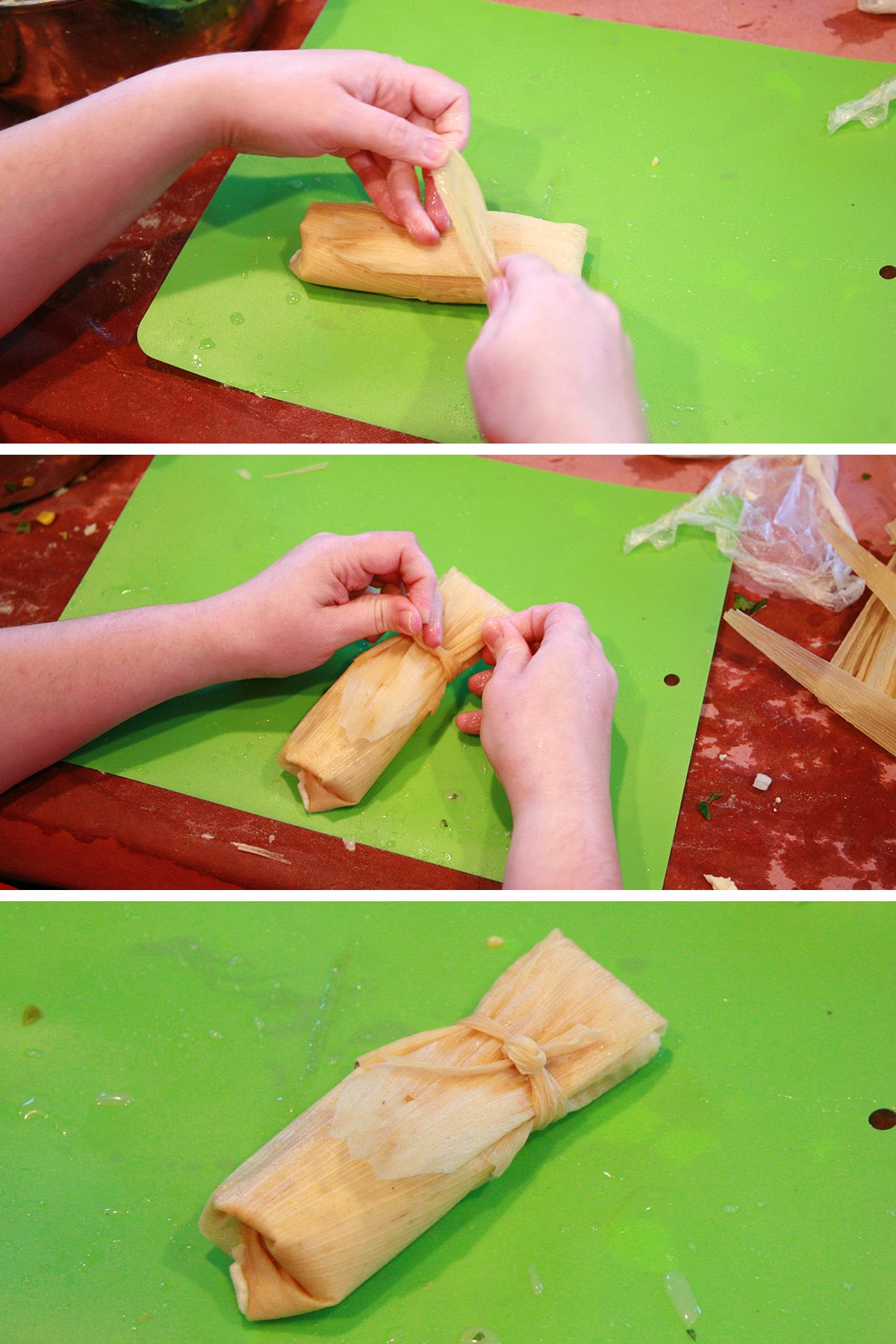 Two hands fold and tie off the tamale, as described.