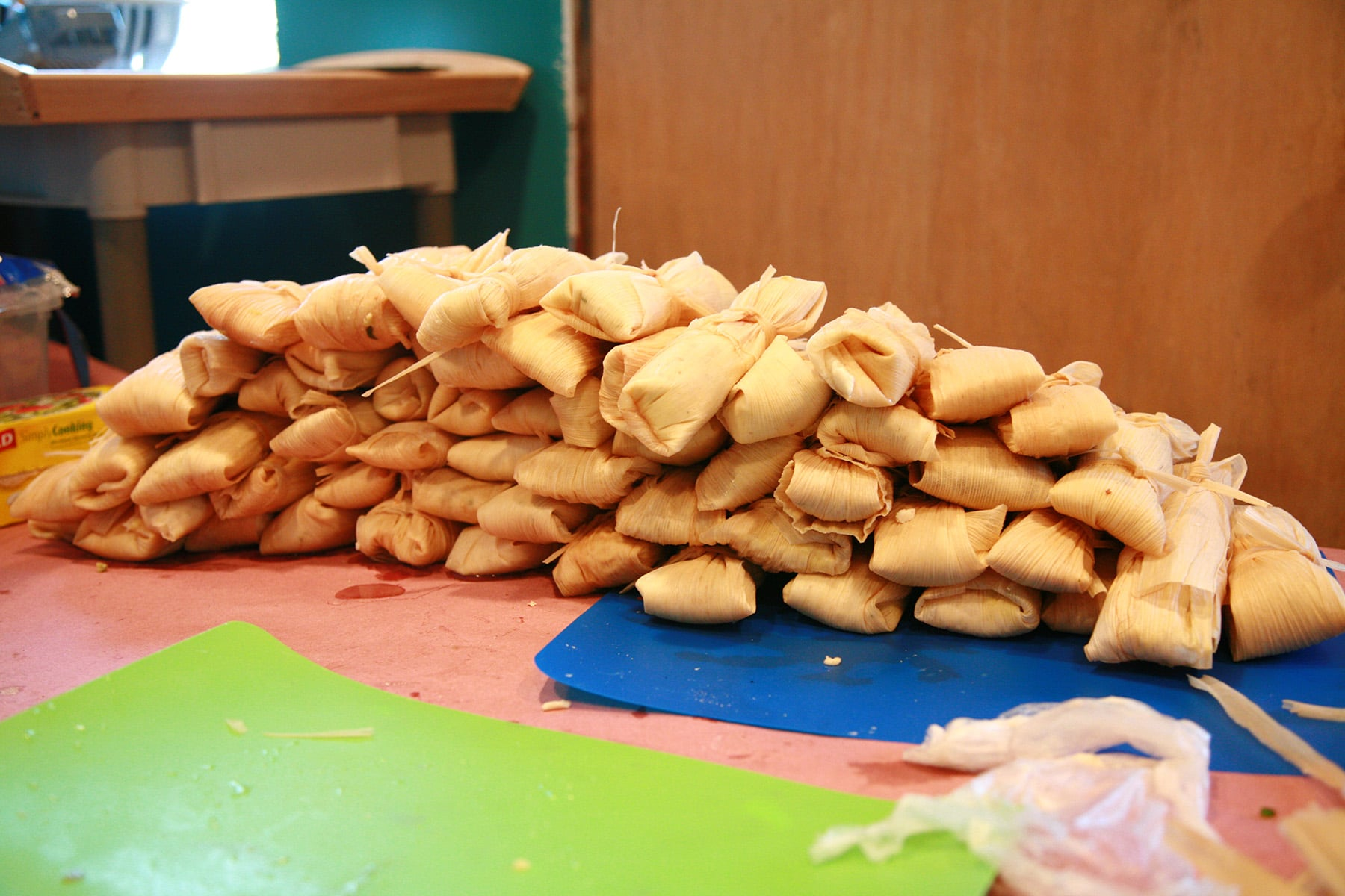 A large pile of wrapped tamales on a work table.