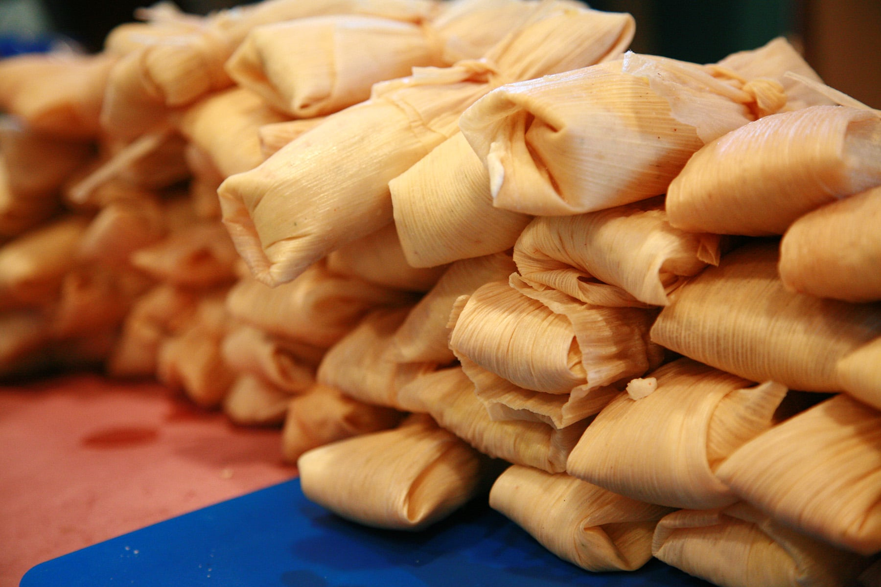 A close up view of a large pile of wrapped tamales on a work table.