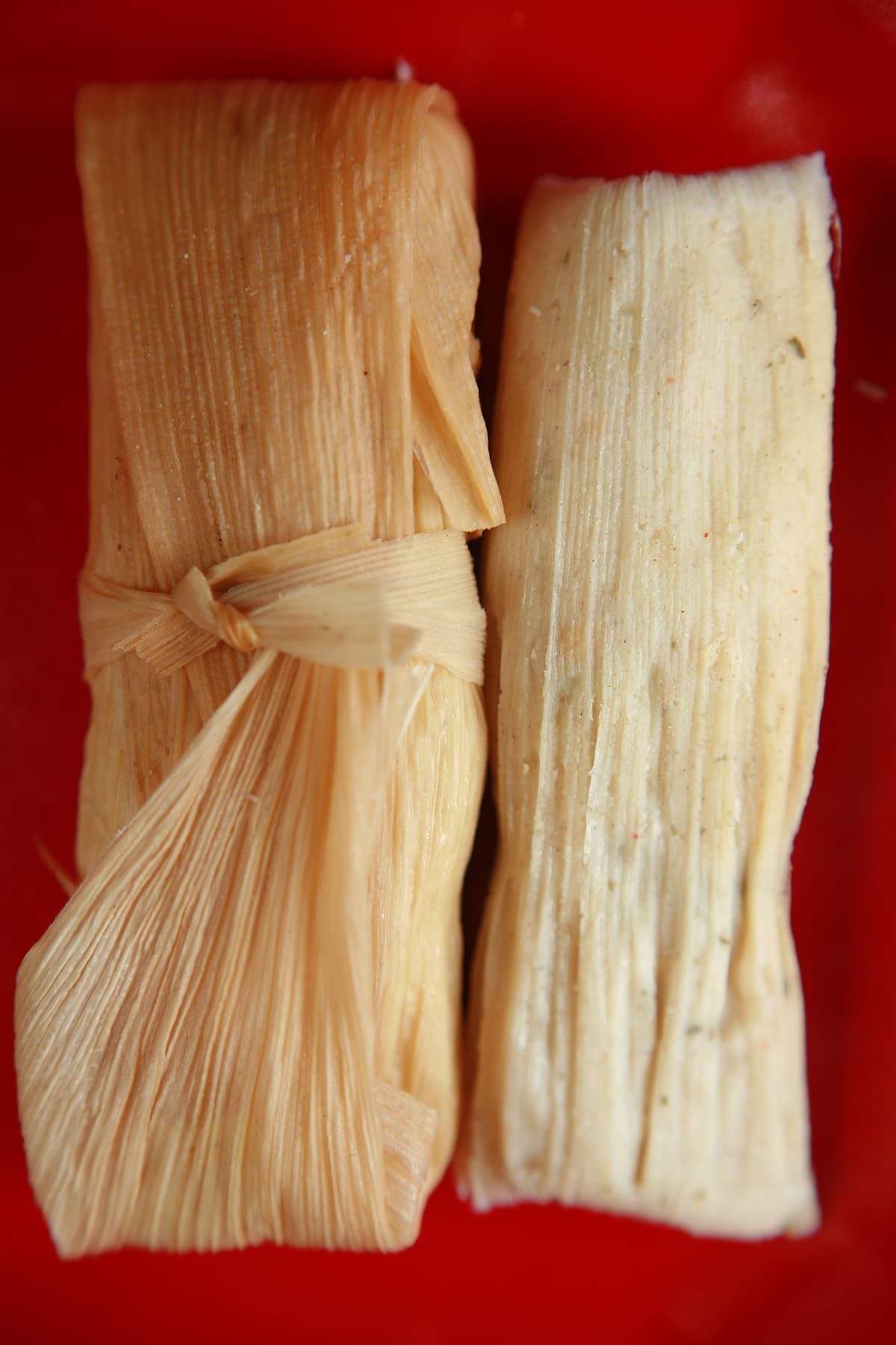 Two salsa verde tamales on a red plate.