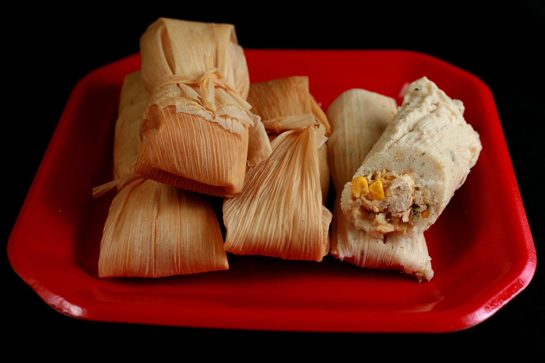 A small pile of salsa verde tamales on a red plate.