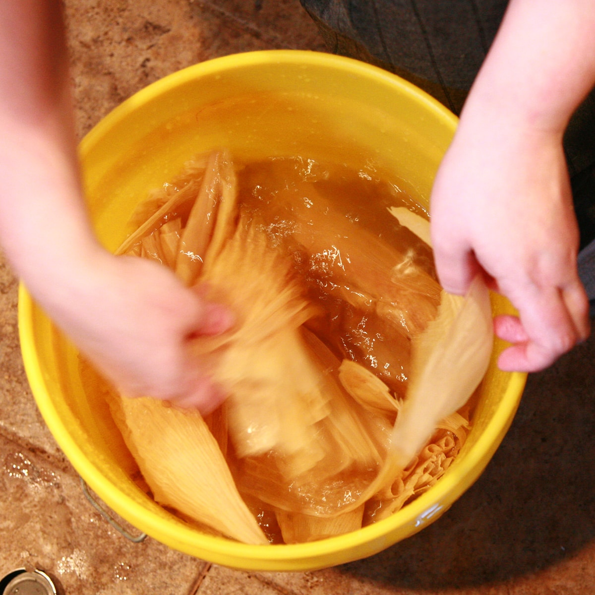 Hands are separating a bag of corn husks, in a large yellow bucket of water.