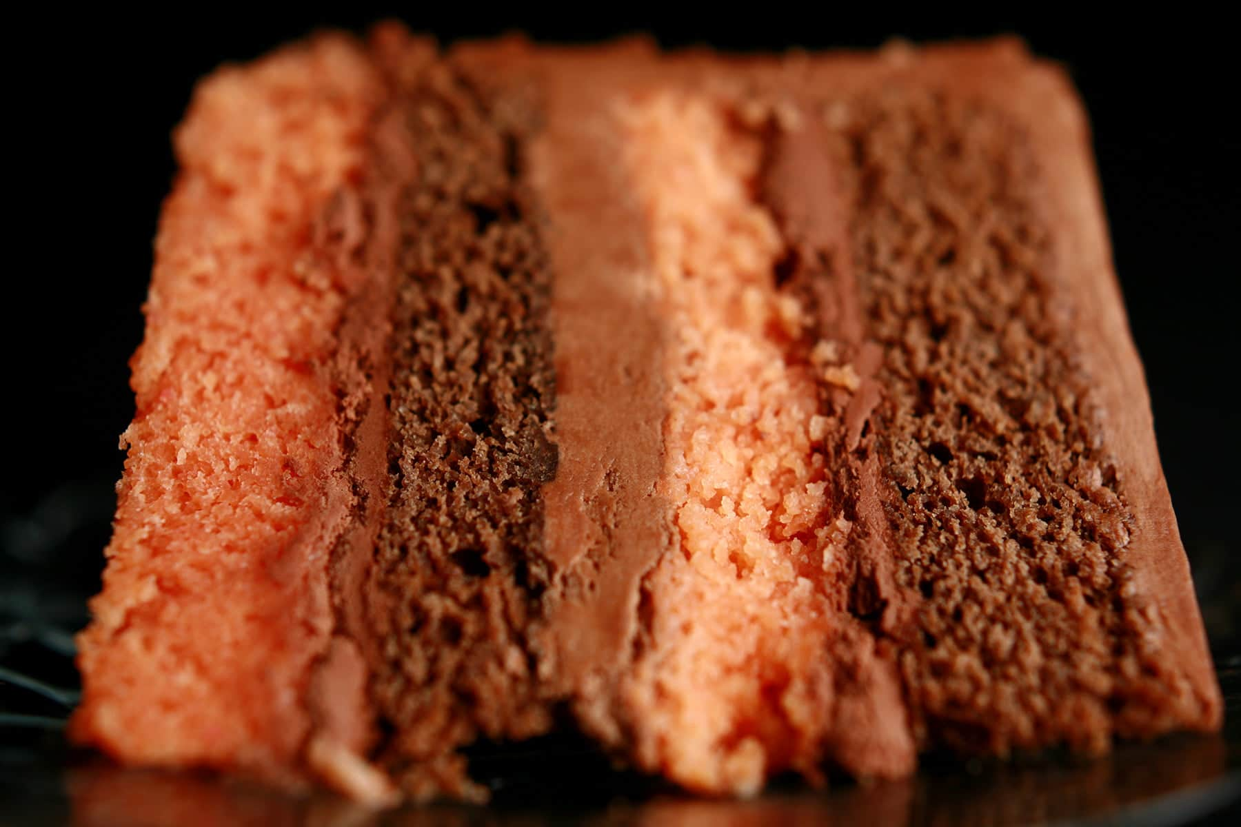 A large slice of B-52 Torte - Layers of mocha and orange cakes, separated by layers of blood orange ganache and Irish Cream buttercream.