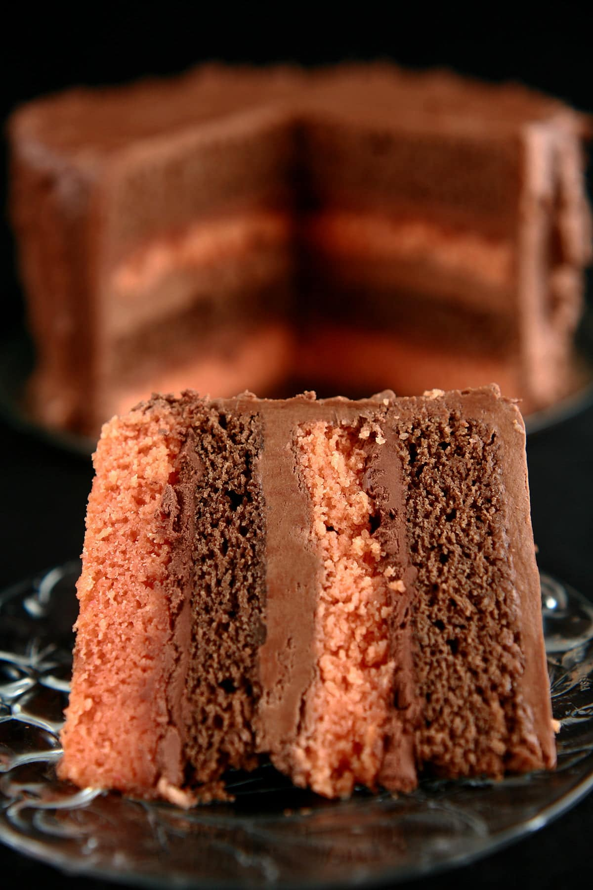 A large slice of B-52 Cake is shown in front of a round, whole cake with a section cut out. The cake shows layers of mocha and orange cakes, separated by layers of blood orange ganache and Irish Cream buttercream.