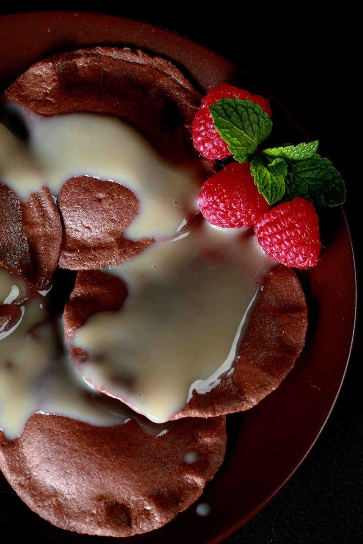 Chocolate Dessert Ravioli, arranged on a dark plate. It is drizzled with a cream sauce, and garnished with raspberries and a mint spring.