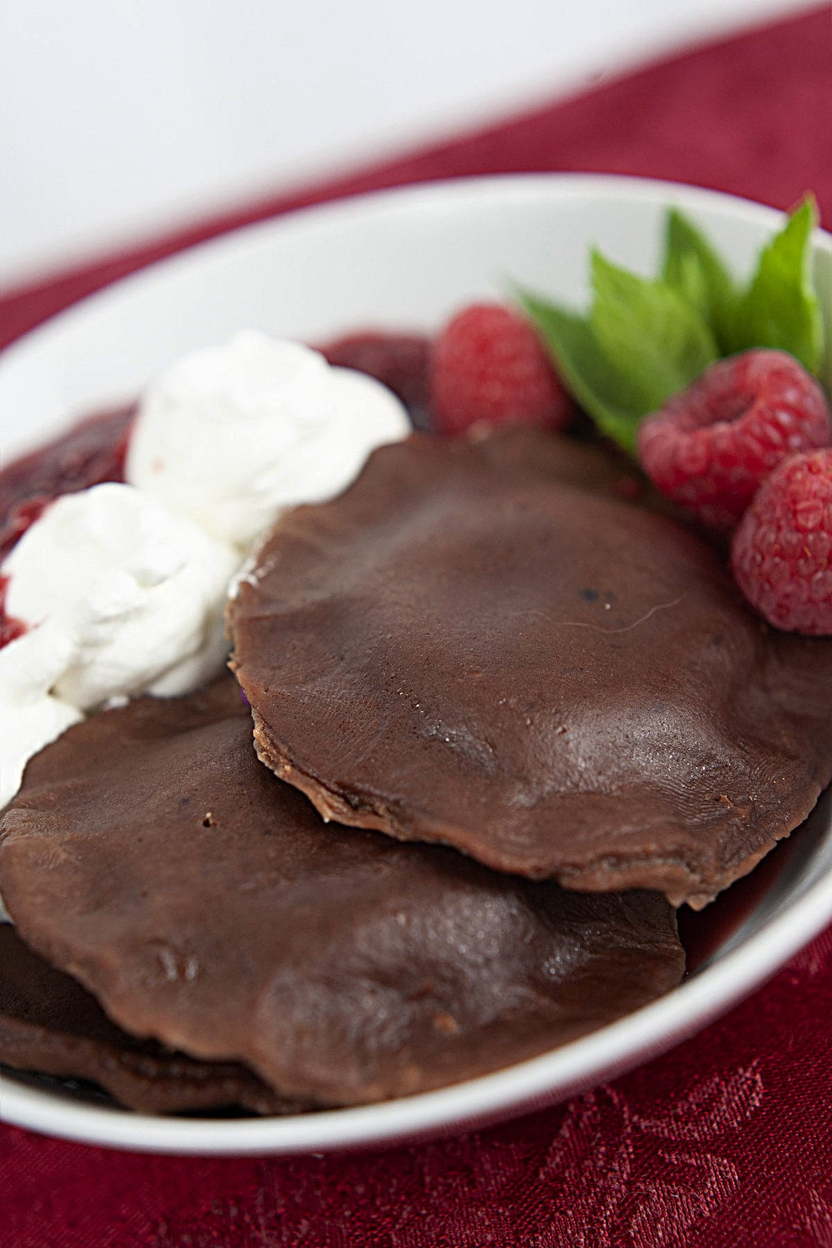 A white bowl holds 2 large chocolate ravioli. There is whipped cream and raspberry sauce on the side, and it is garnished with raspberries and mint.