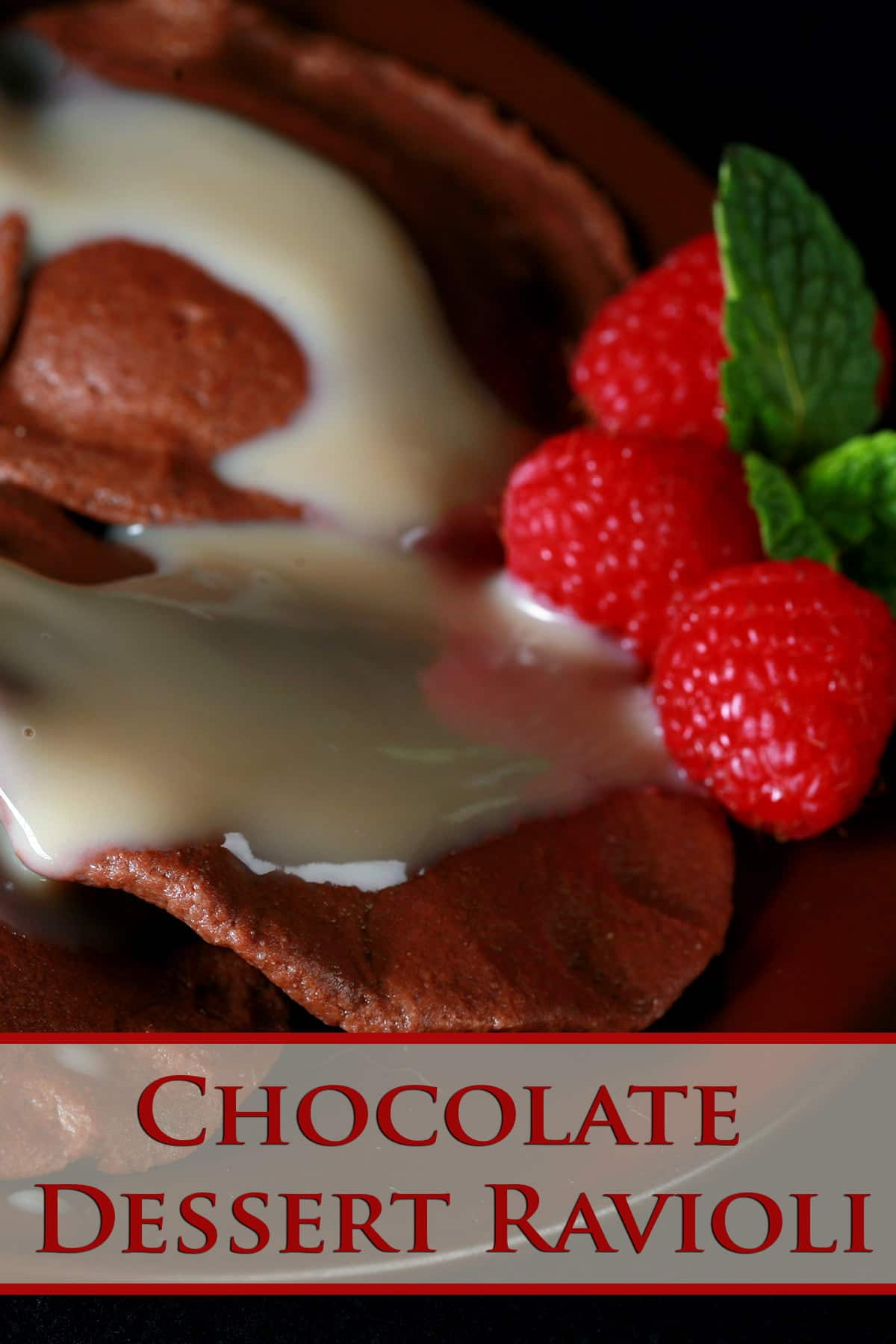 Chocolate Ravioli, arranged on a dark plate. It is drizzled with a cream sauce, and raspberries and a mint spring.
