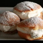 3 Large Cream puffs - with whipped cream in the center, topped with powdered sugar - are pictured on a white plate.