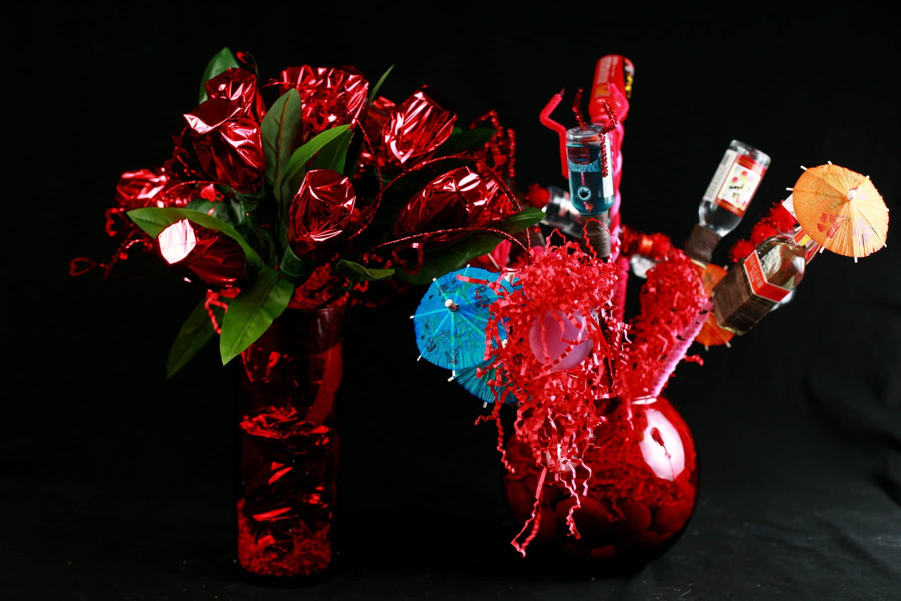 "A close up view of a ""bouquet"" made from mini booze bottles.  Each are wrapped in wire and adored with things like pipe cleaners, mini umbrellas, and pom poms.  It is next to a second bouquet, made of mylar wrapped mini booze bottles."