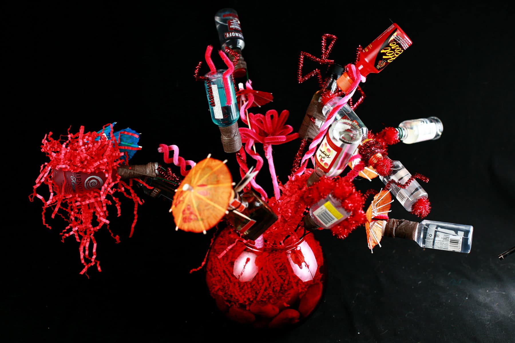 "A close up view of a ""bouquet"" made from mini booze bottles.  Each are wrapped in wire and adored with things like pipe cleaners, mini umbrellas, and pom poms."