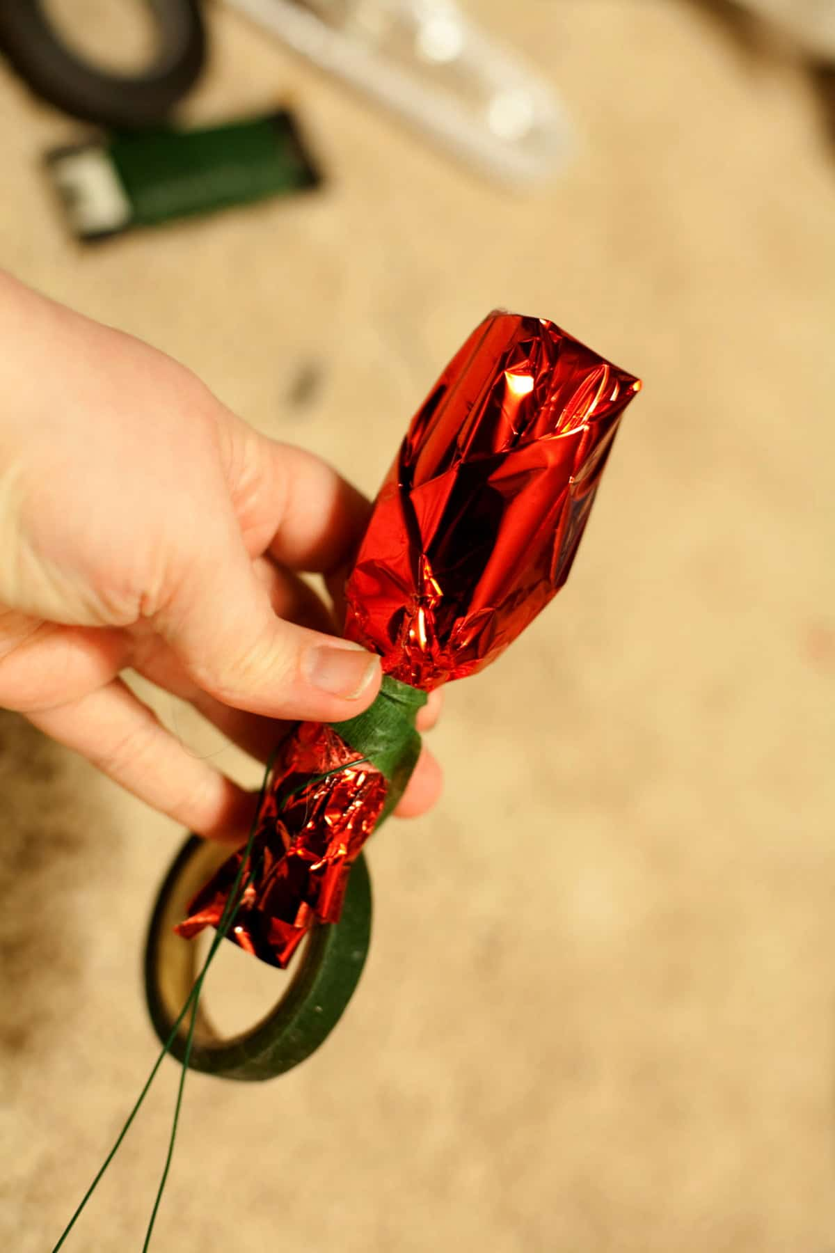 A hand is shown wrapping red mylar tightly around a mini liquor bottle.
