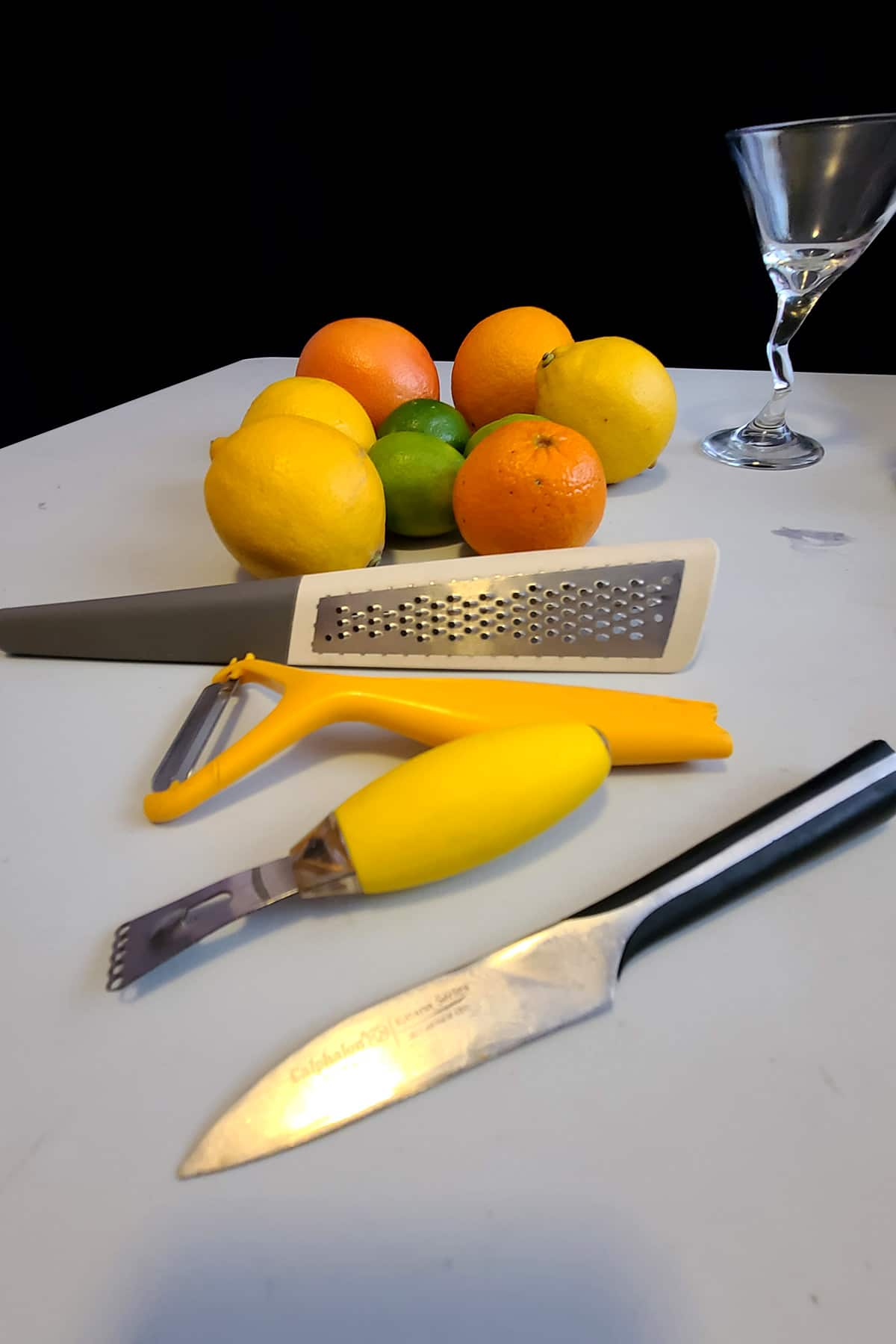 A grouping of lemons, limes, and oranges on a white cutting board. A zester, peeler, channel knife, and paring knife are in the foreground.
