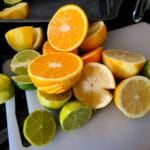 A grouping of lemons, limes, and oranges on a white cutting board. All have been cut in half.