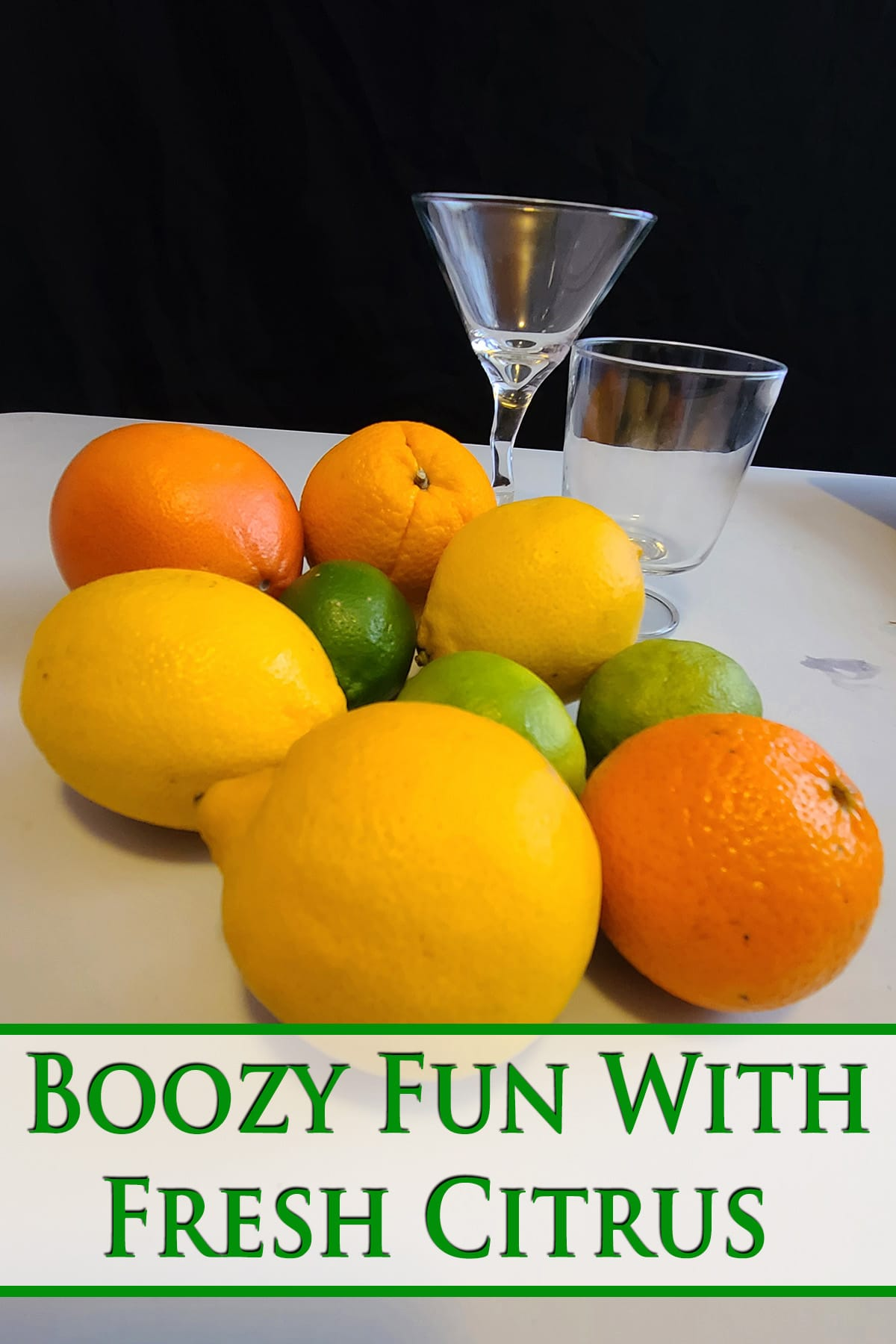 A grouping of lemons, limes, and oranges on a white cutting board. Green text overlay says boozy fun with fresh citrus.