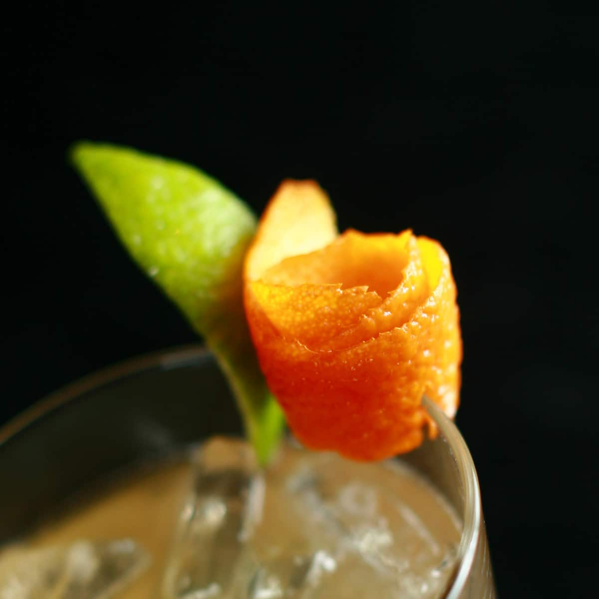 A close up photo of a citrus peel rose garnish on the edge of a cocktail glass.