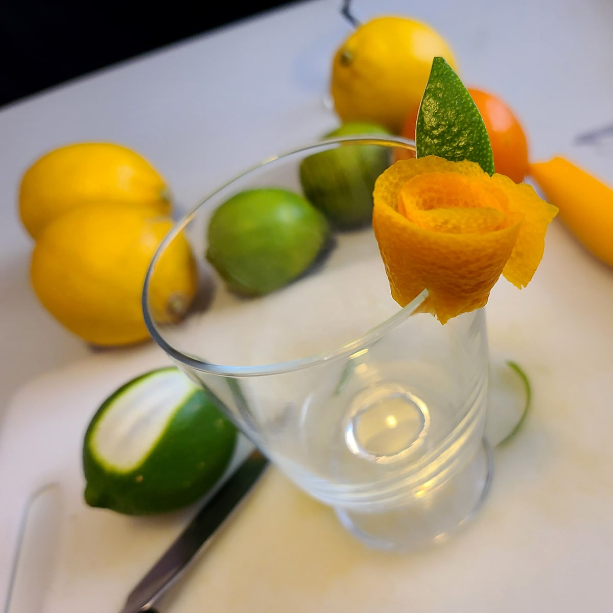 A citrus peel rose garnish on the edge of a cocktail glass.