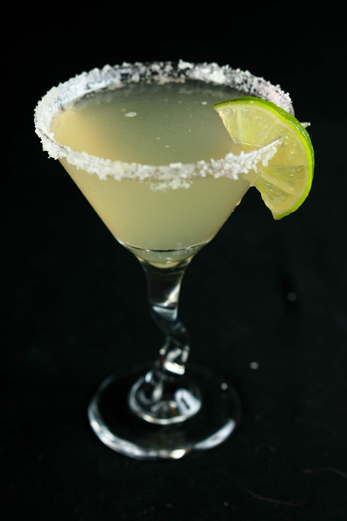 A margarita, garnished with salt rim and a lime slice.