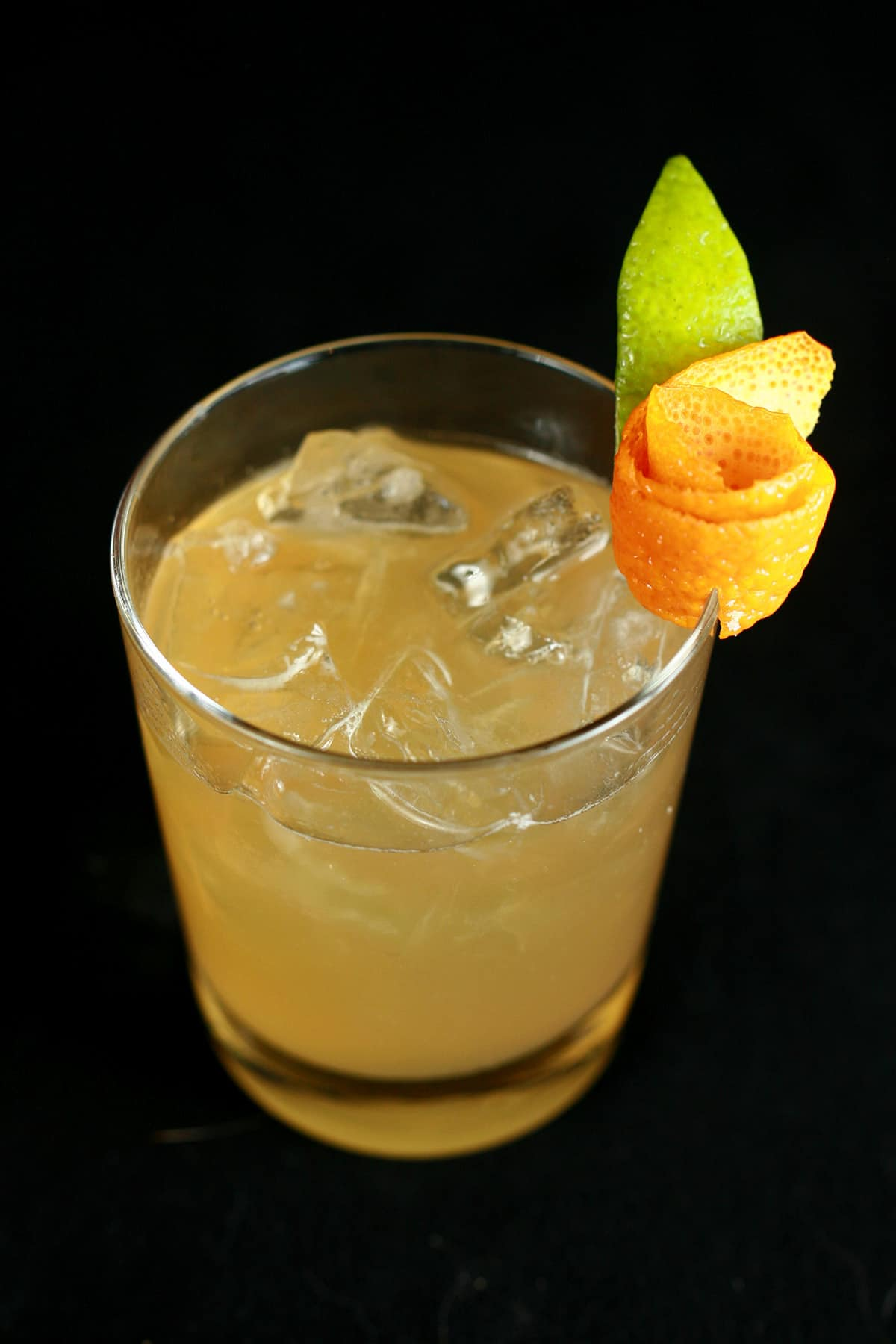 A small glass of amaretto sour, garnished with a citrus rose.