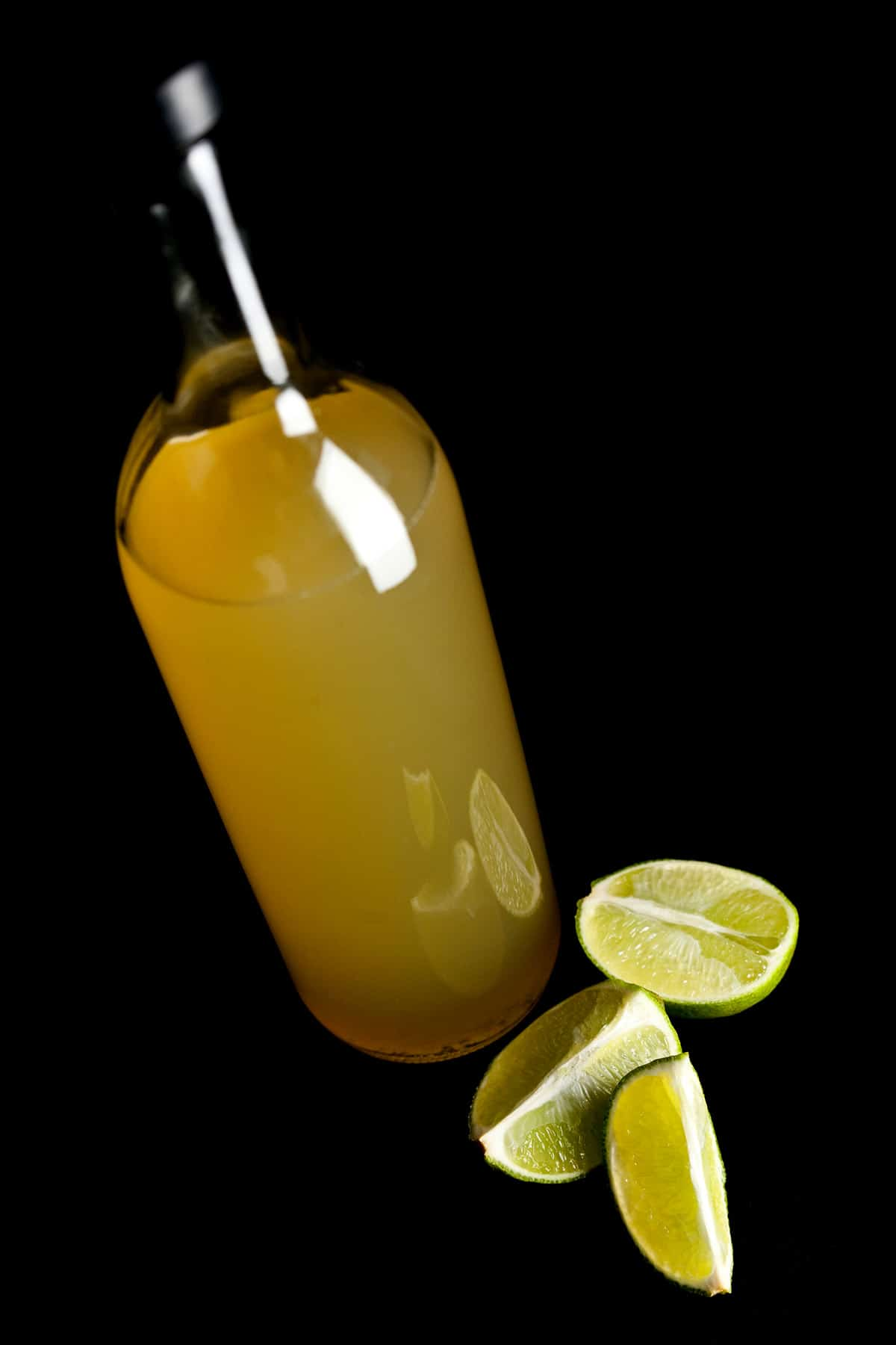 A bottle of homemade sour mix, with sliced limes at its base.
