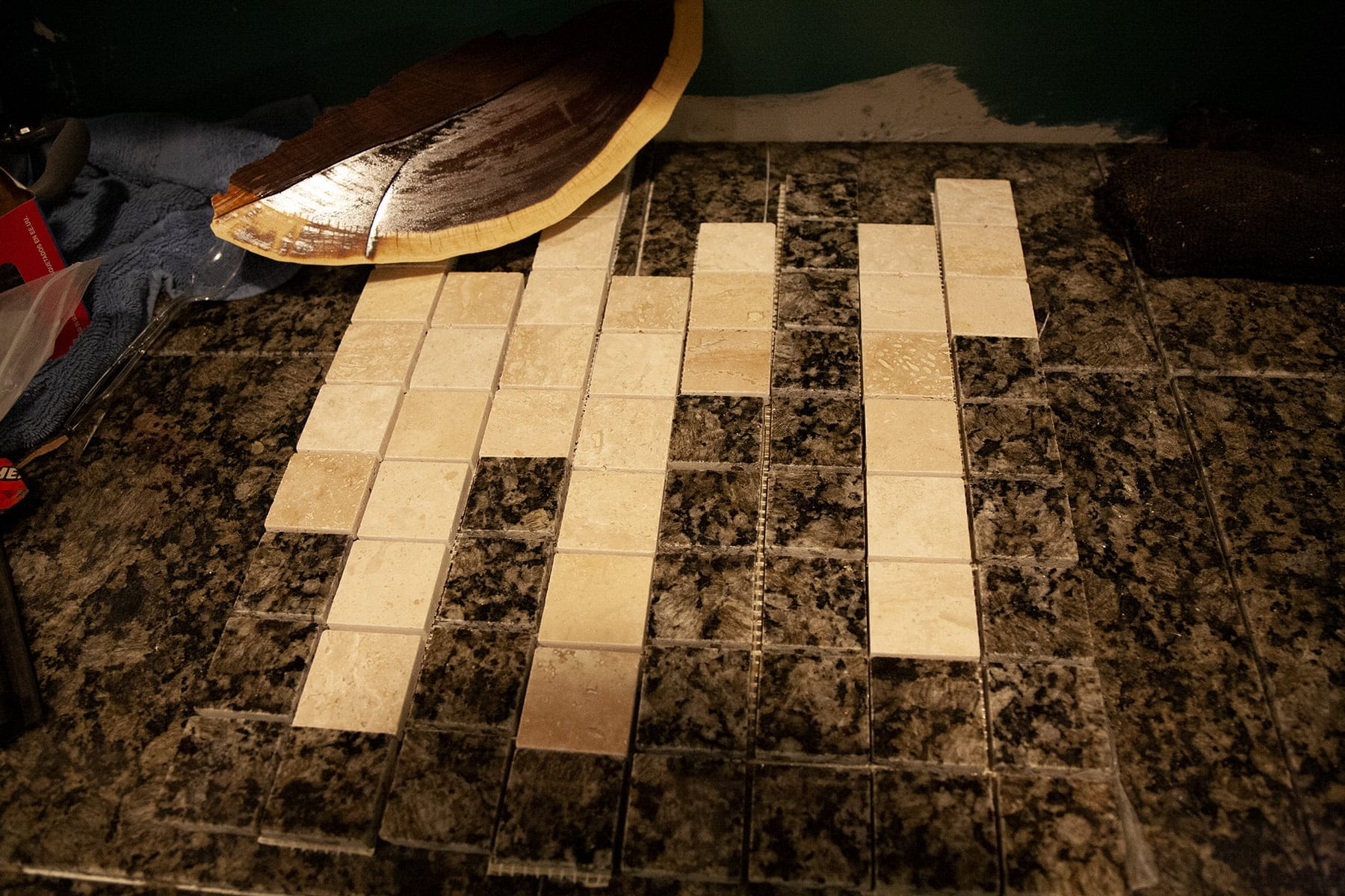 Columns of pre-cut strips of granite backsplash tiles are laid out on a counter.