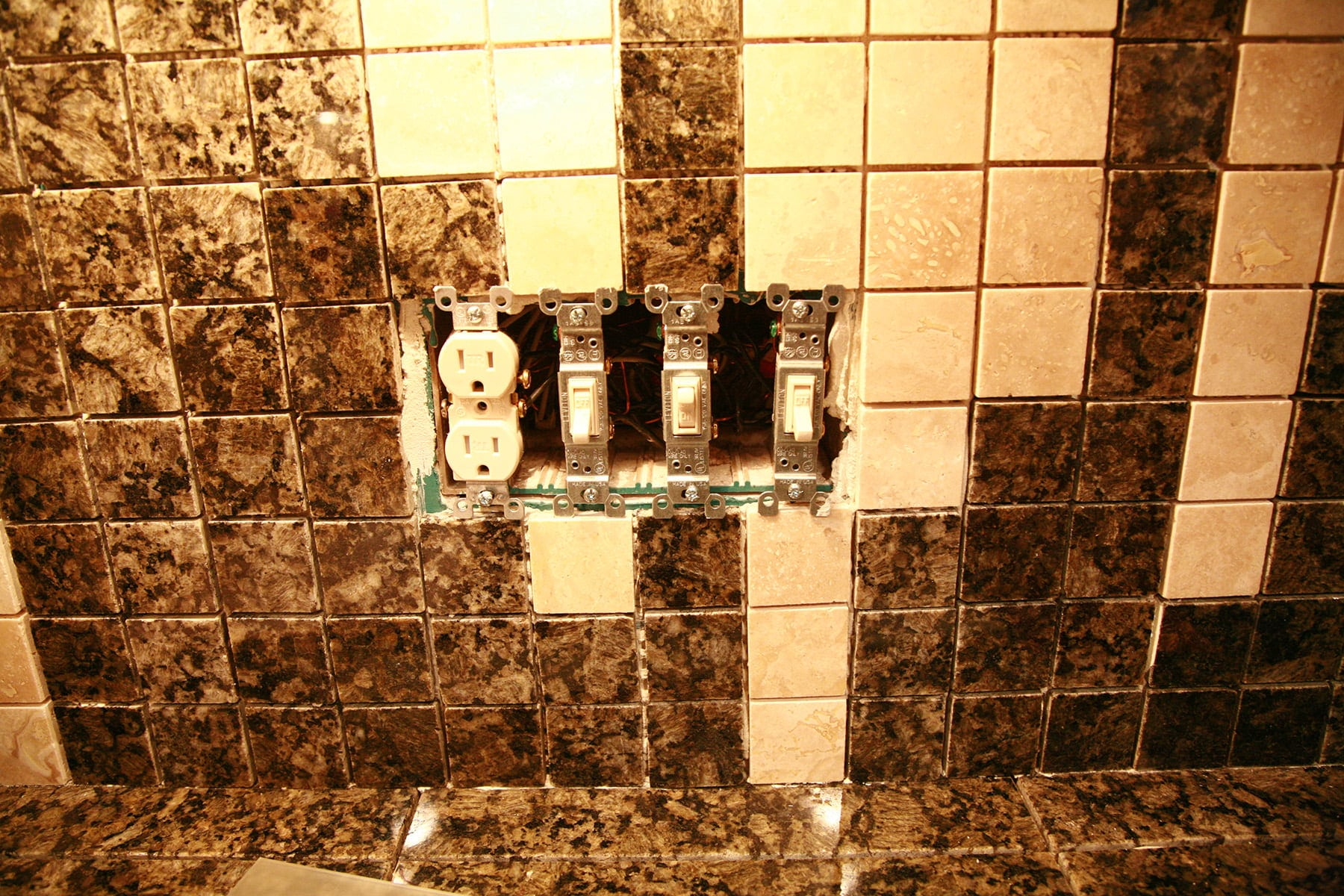 A exposed light switch panel is surrounded by green and white squares of granite tile.