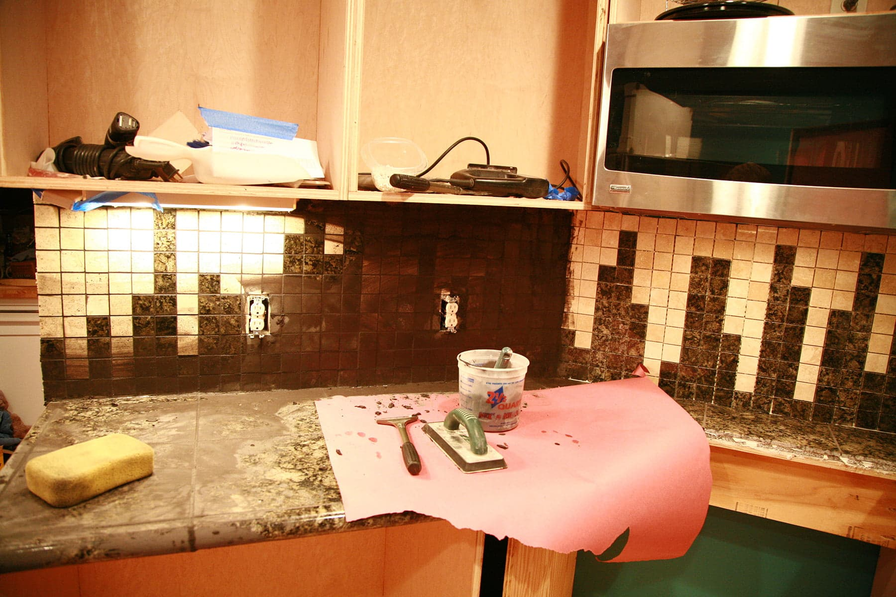 A counter is covered with pink rosin paper, and the back splash has black grout applied over the whole surface. Grout tools are visible in the foreground.