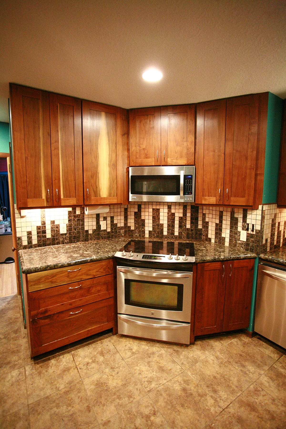 A full view of a section of kitchen. The floor is brown and mottled looking, the cabinetry is black walnut, the walls are teal, the appliances are stainless steel, and the backsplast and counter is in dark granite with lighter accents on the backsplash.
