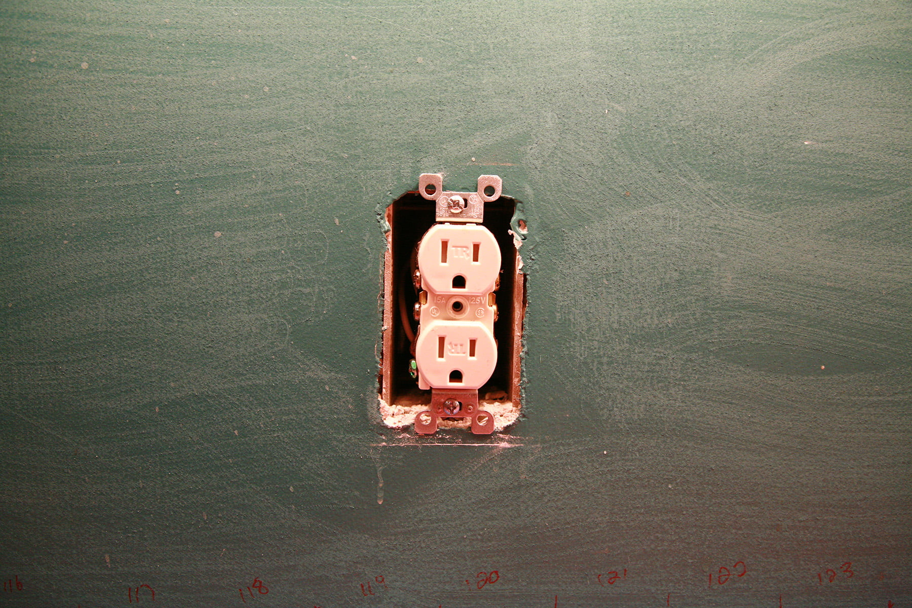 A bare electrical outlet is surrounded by wall that has been sanded.