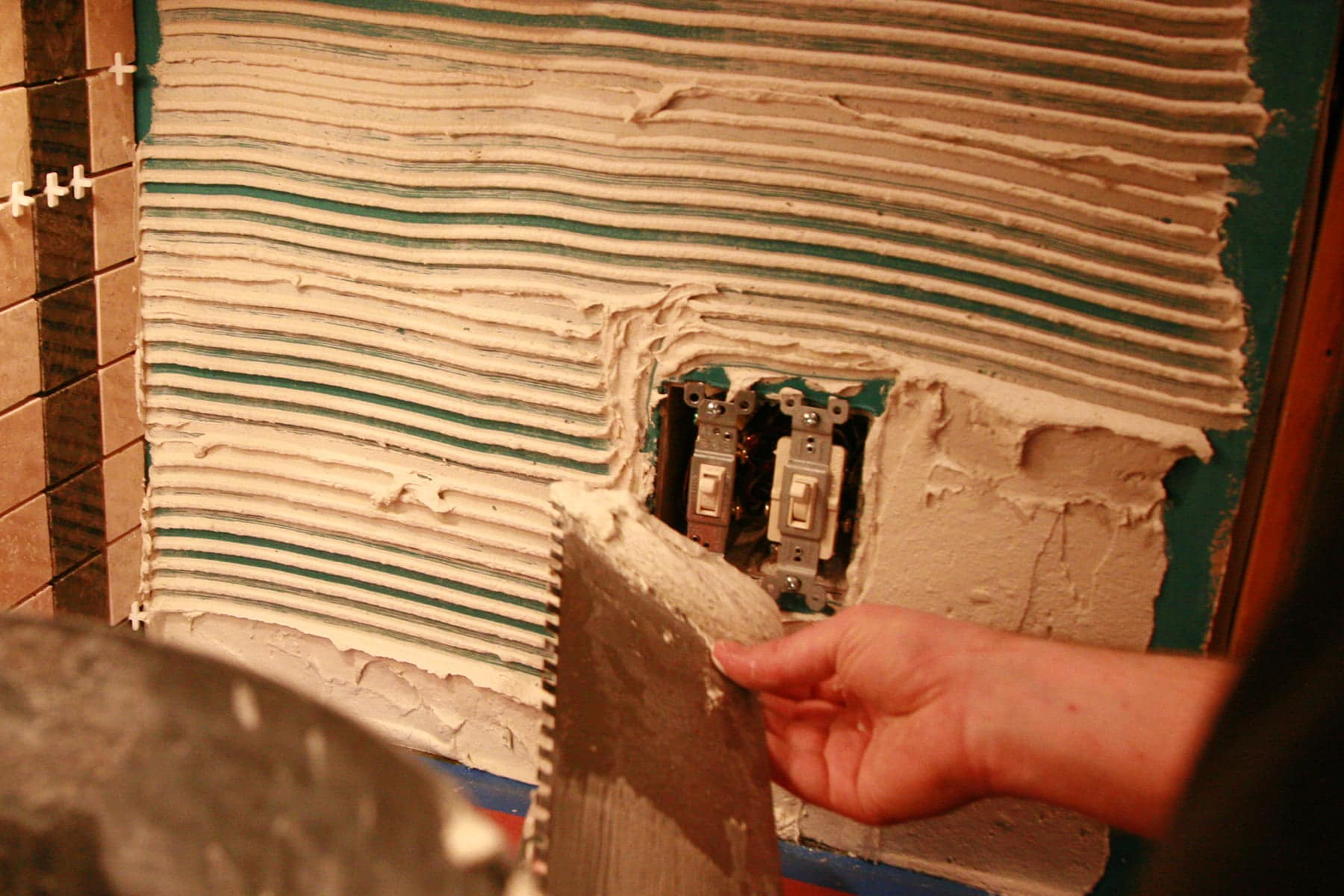 A hand applies tile adhesive to a wall with a flat metal tool.