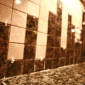 A close up view of a section of granite tile backsplash. The square tiles are held apart with little white spacers.