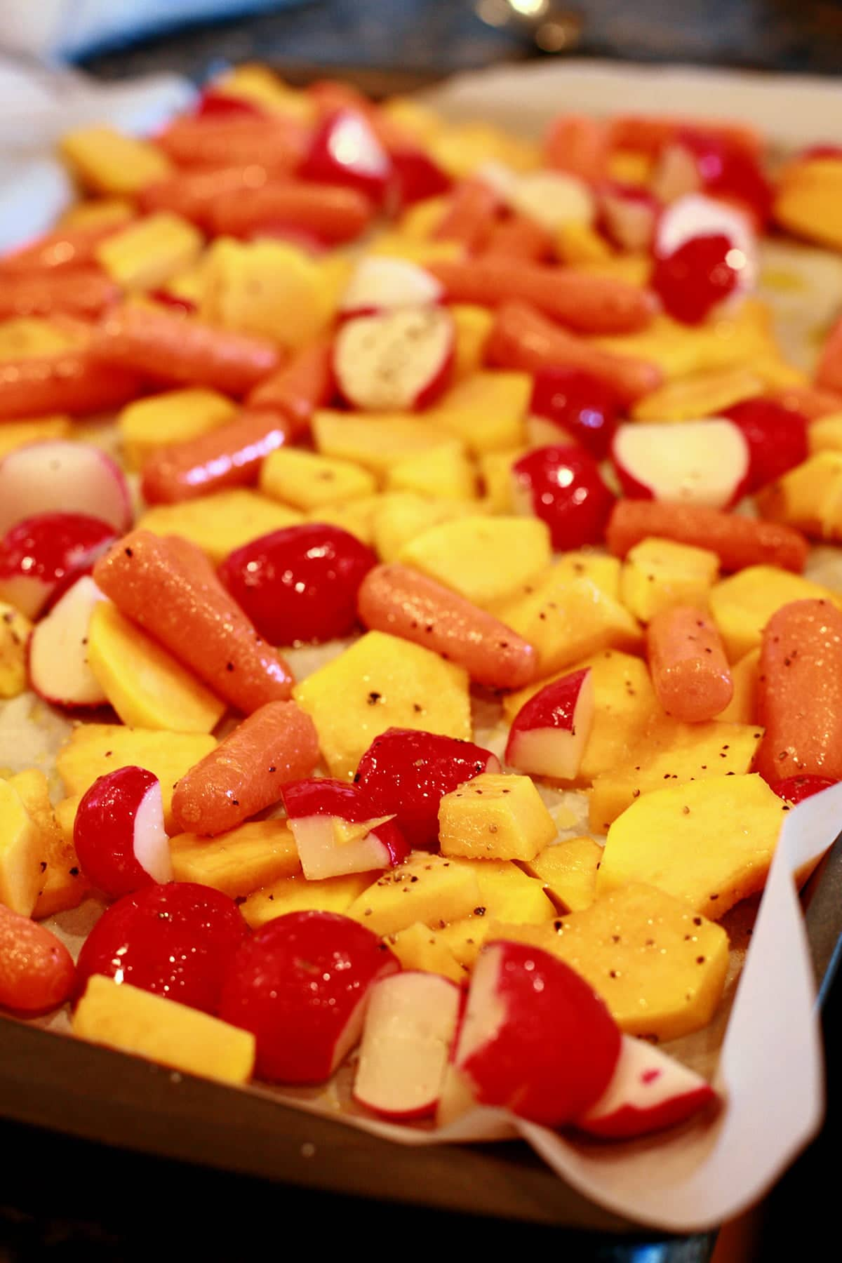 A parchment lined baking sheet is covered with chopped radishes, squash, and baby carrots,