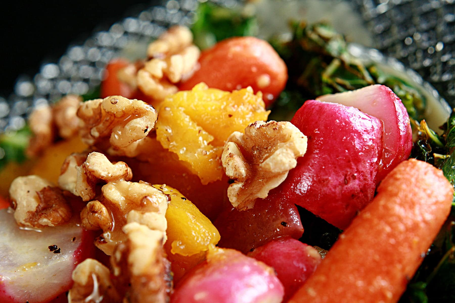 Roasted Radish Salad on a glass plate. Roasted radishes, baby carrots, and squash are served on a base of crispy kale, and topped with a dijon vinaigrette and walnuts.