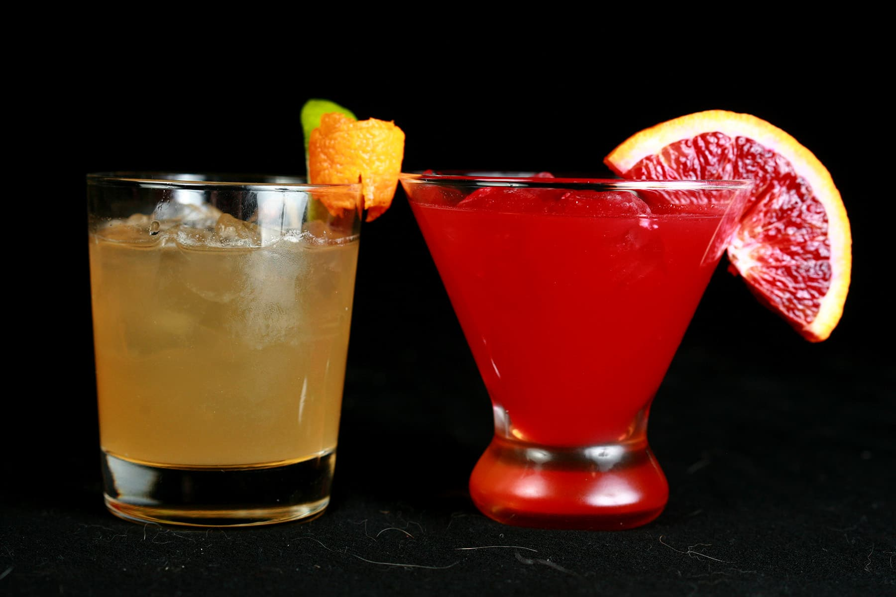 Two glasses of sours cocktails, one made with a traditional lime recipe, and the other with blood orange.