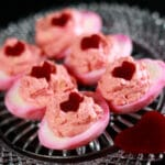6 pink tie dyed deviled eggs on a glass plate. Each is topped with a heart shaped piece of pickled beet.