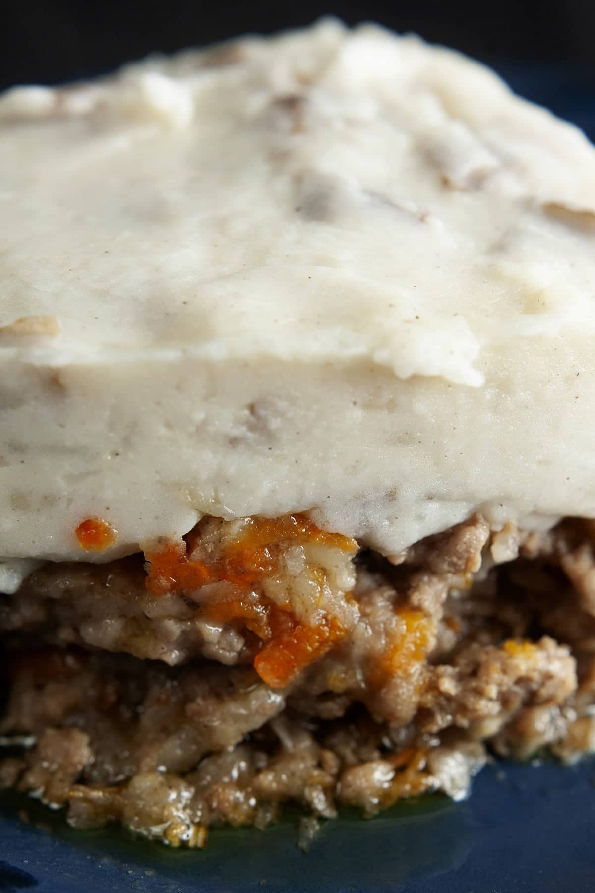 A square serving of shepherd's pie is centered on a blue plate.  Carrots and parsnips are visible in the meat/veg base, and it's topped with a thick layer of mashed potatoes.