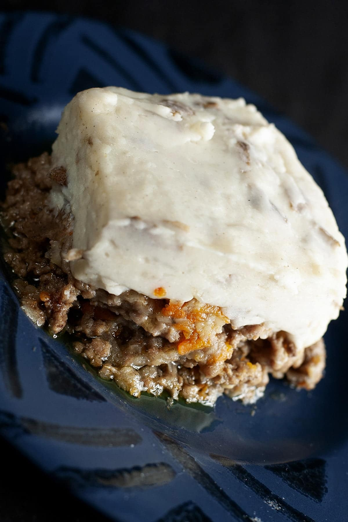 A square serving of cottage pie is centered on a blue plate. Carrots and parsnips are visible in the meat/veg base, and it's topped with a thick layer of mashed potatoes.