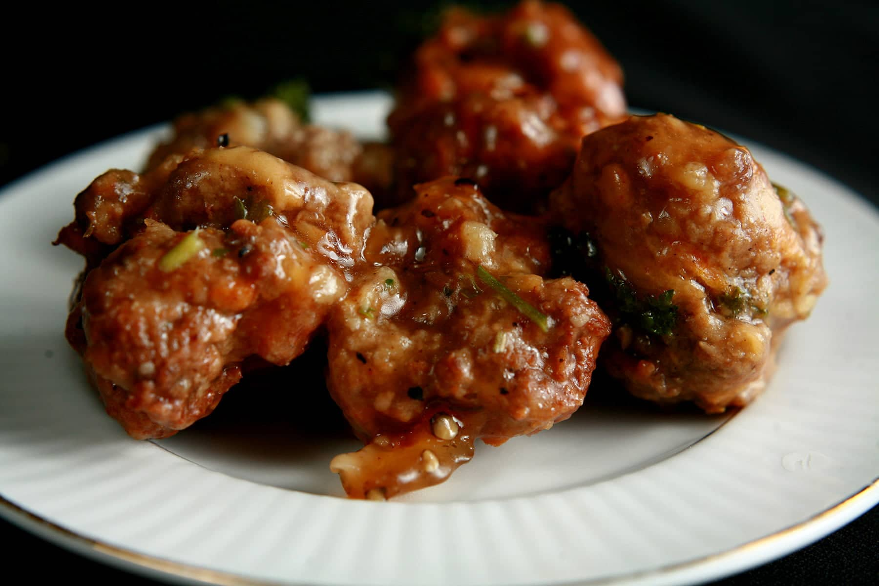 Several Gluten-Free Irish Stew Meatballs are served on a small white plate. The meatballs show flecks of orange and green throughout.