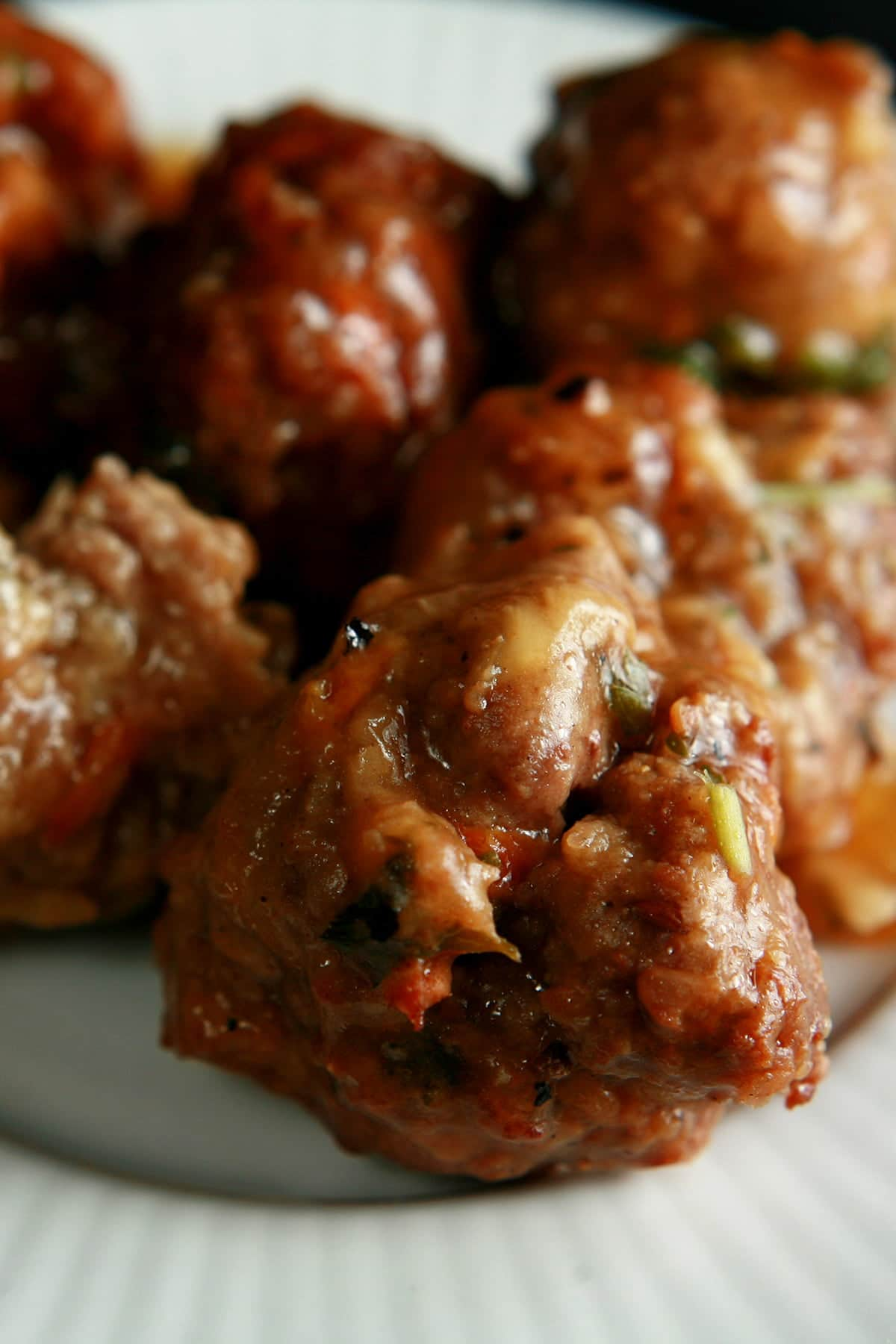 Several Gluten-Free Meatballs are served on a small white plate. The meatballs show flecks of orange and green throughout.