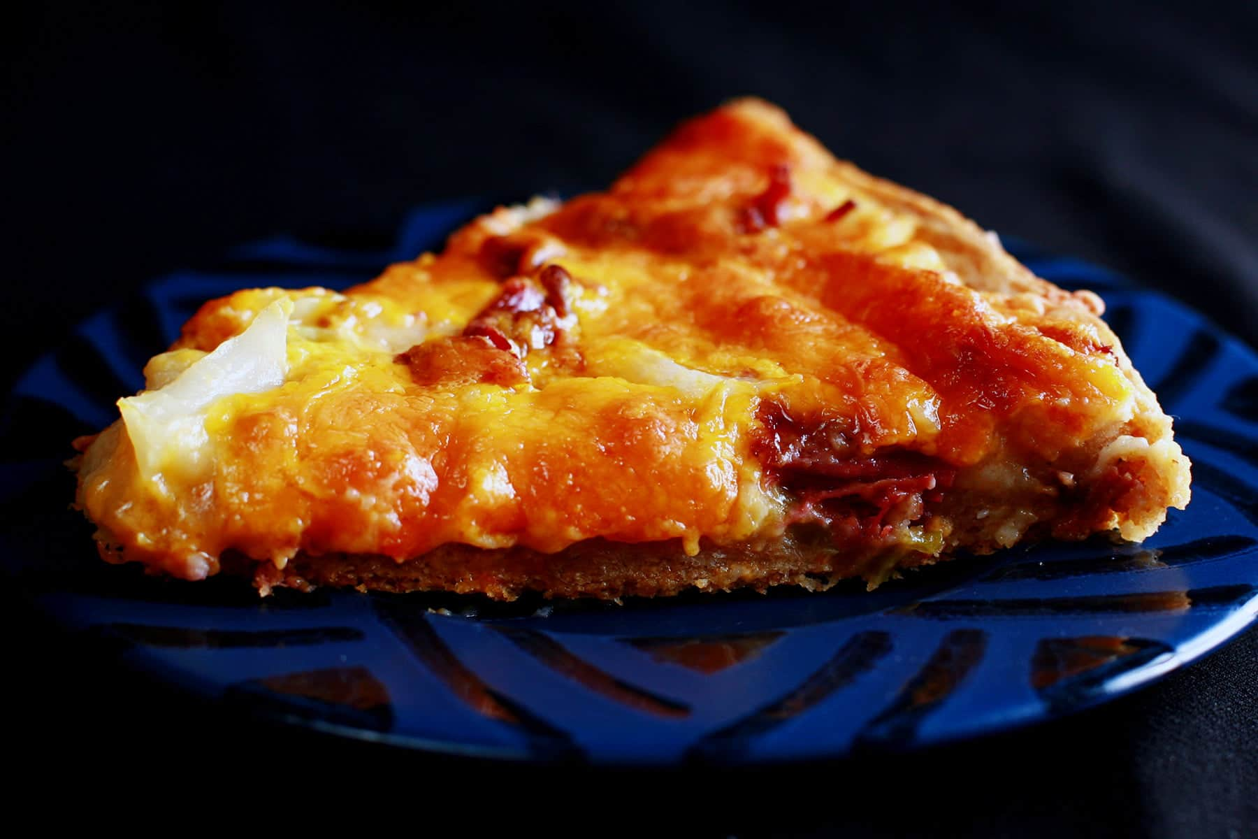 A slice of St Patrick's Day Pizza on a blue plate. Chunks of cabbage and corned beef are visible from under the cheese.