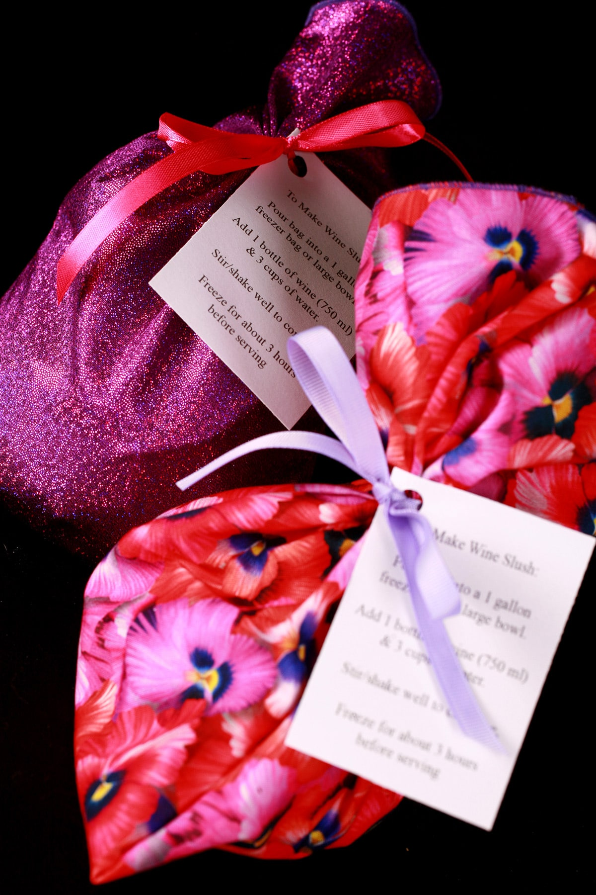 Two gift bags - in the foreground, a pink and purple floral fabric bag, in the background is a bag made from purple hologram fabric. Each bag is tied with a bow, and has a little card with instructions on it.