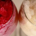 A close up view of two glasses of slush, made from Homemade Wine Slush mix. One glass is full of a deep pink-red slush, and the other has white wine slush.