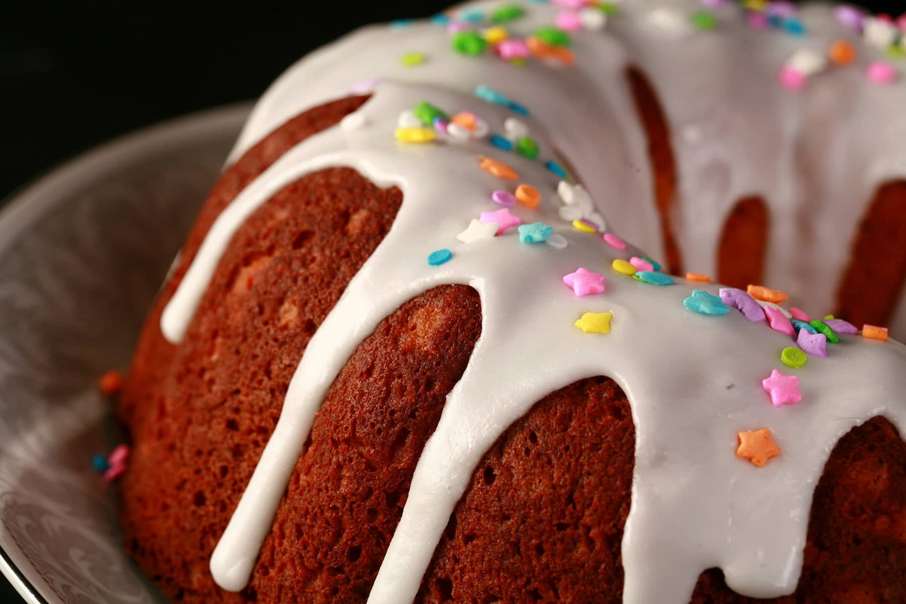 A close up view of a gluten-free paska. It's in the shape of a bundt pan, with dripping white glaze and topped with pastel coloured sprinkles.