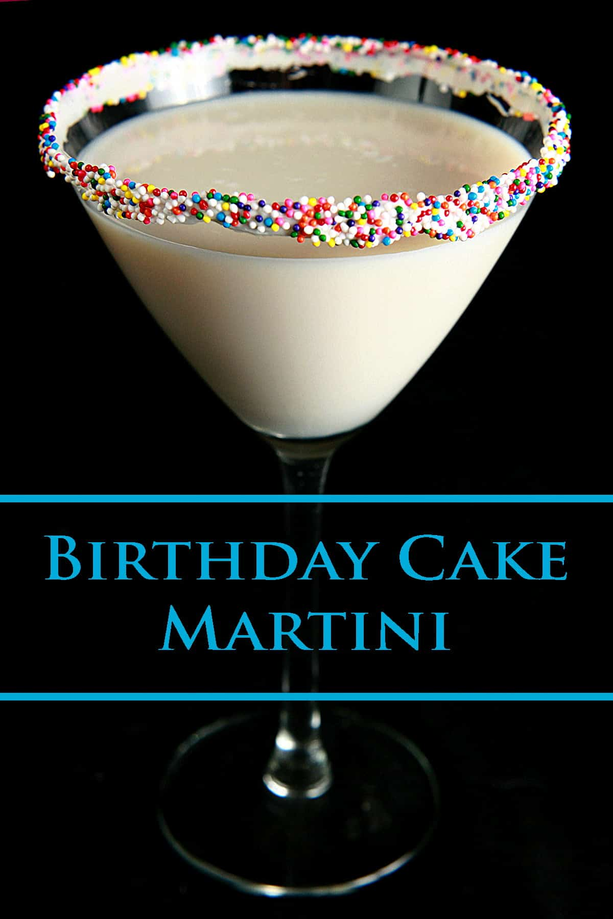 A close up view of a birthday cake martini - a creamy white drink in a martini glass. The rim is coated with colourful nonpareils.