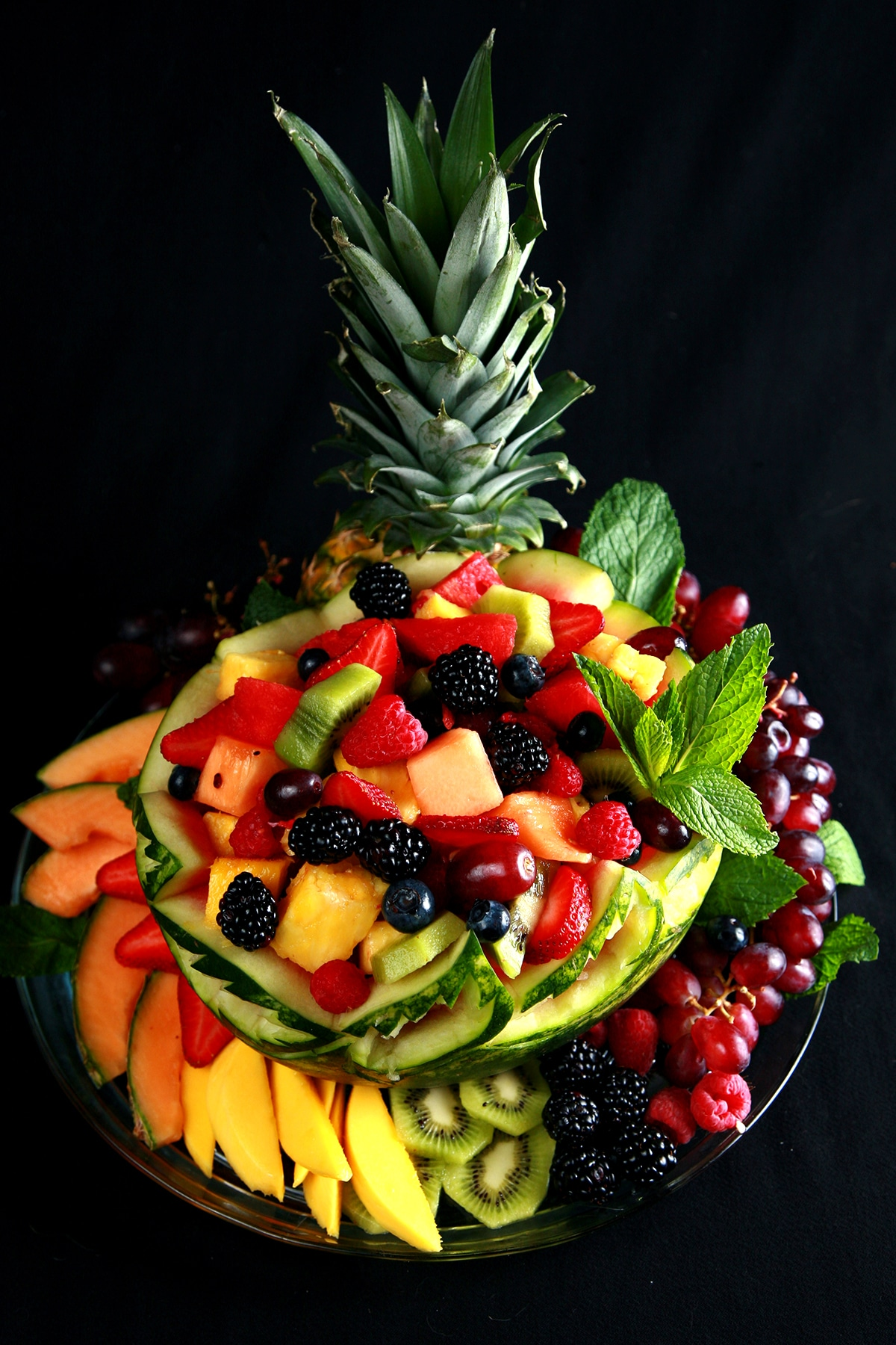 A large, brightly coloured watermelon bowl display. The watermelon is carved with a Caladium Leaf design, and is filled and surrounded by a rainbow assortment of fruit.