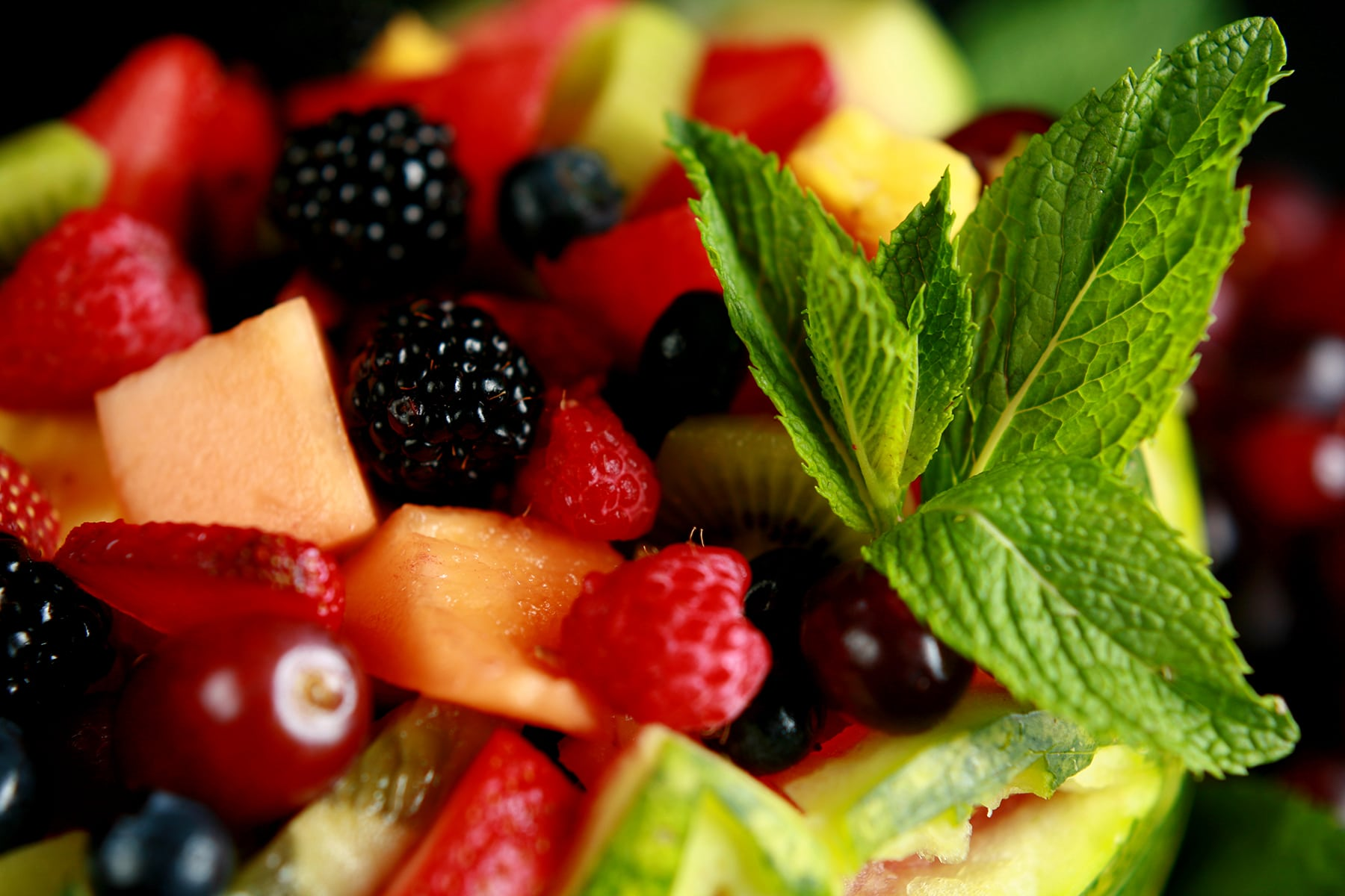 A close up view of a fruit salad, garnished witha  sprig of mint.